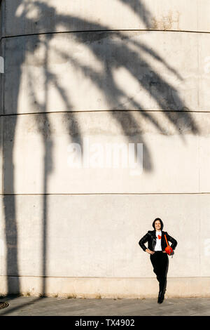 Happy young woman with a red hip bag resting on a wall with the shadow of a palm tree. - Stock Photo