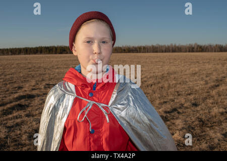 Portrait of boy dressed up as superhero in steppe landscape blowing a chewing gum bubble