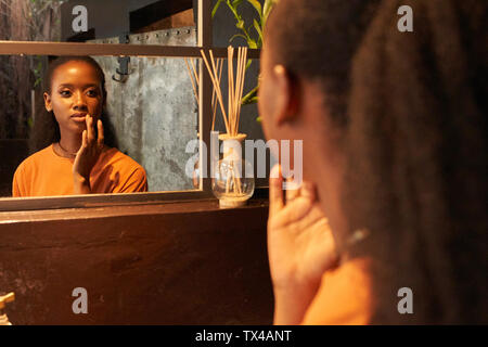 Young woman looking in bathroom mirror - Stock Photo