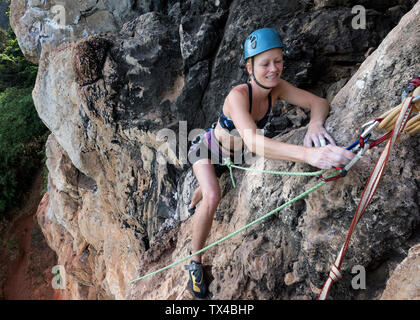 Thailand, Krabi, Thaiwand wall, smiling woman climbing in rock wall - Stock Photo