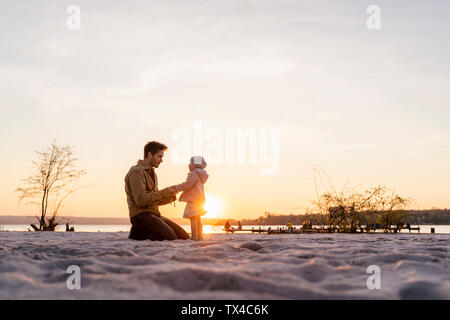 Germany, Bavaria, Herrsching, father and daughter playing on the beach at sunset - Stock Photo