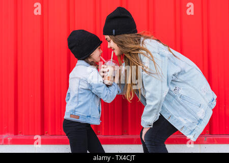 Teenage girl and little sister having fun together - Stock Photo