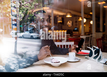 Portrait of smiling young man with earphones and smartphone behind windowpane in a restaurant