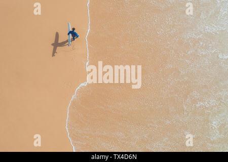 Portugal, Algarve, Sagres, Praia da Mareta, aerial view of man carrying surfboard on the beach