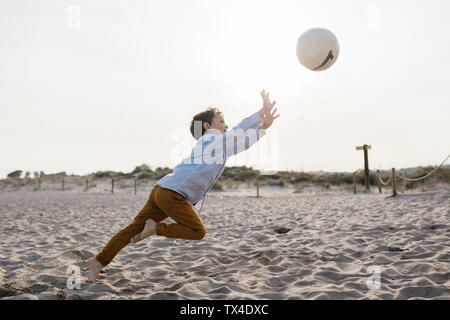 Little boy playing soccer on the beach Stock Photo