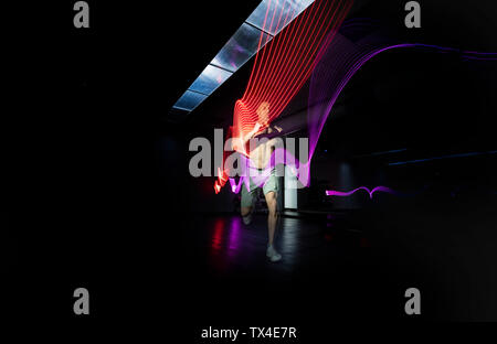 Athlete running in dark area surrounded by colored lights - Stock Photo