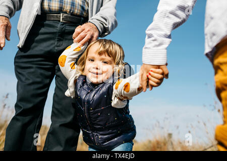 Portrait of happy little girl strolling with  grandfather and brother hand in hand in nature