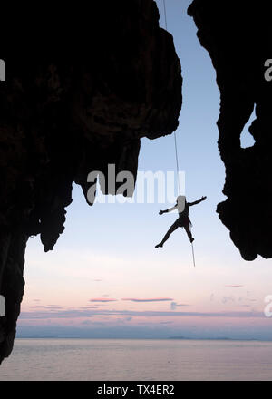 Thailand, Krabi, Lao Liang island, climber abseiling from rock wall above the sea - Stock Photo