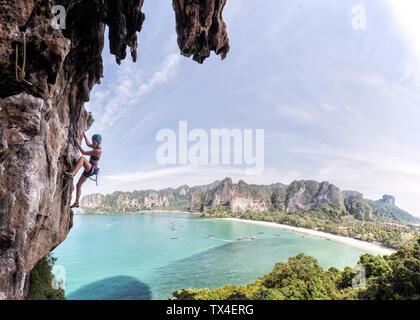 Thailand, Krabi, Thaiwand wall, woman climbing in rock wall above the sea - Stock Photo