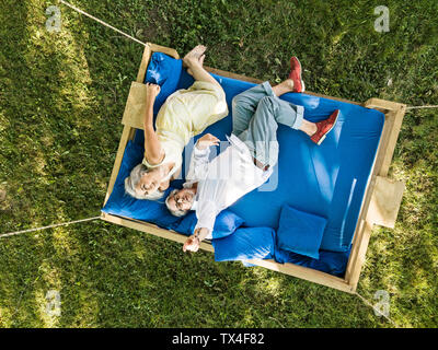 Elderly couple lying on swing bed, watching drone - Stock Photo