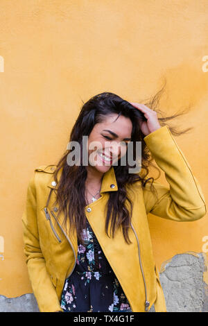 Portrait of young laughing woman wearing yellow leather jacket, hand in hair Stock Photo