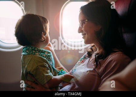 Happy mother and little daughter on airplane