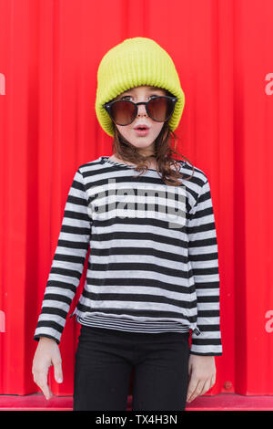 Portrait of astonished little girl wearing striped shirt, yellow cap and oversized sunglasses - Stock Photo