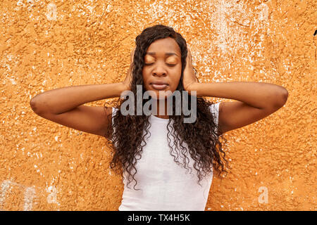 Portrait of young woman covering  ears with her hands