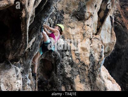 Thailand, Krabi, Thaiwand wall, woman climbing in rock wall - Stock Photo