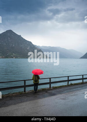 Italy, Lombardy, back view of senior woman with backpack and red umbrella looking at Lake Idro - Stock Photo