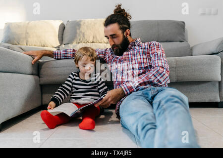 Father and little daughter sitting in the floor in the living room reading a book together - Stock Photo