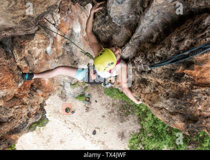 Thailand, Krabi, Lao liang island, woman climbing in rock wall - Stock Photo