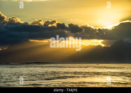 French Polynesia, Tahiti, sunrays breaking through the clouds over Moorea - Stock Photo