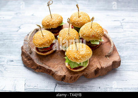 Mini-Burger with mincemeat, salad, cucumber and tomato on wooden tray - Stock Photo