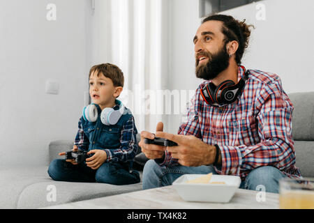 Portrait of father and son sitting together on the couch playing computer game - Stock Photo