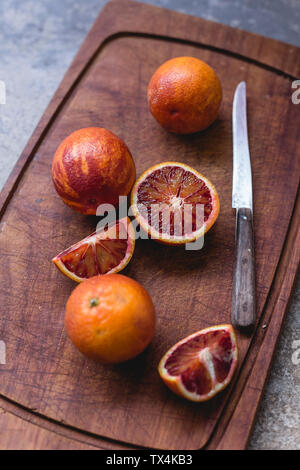 Whole and sliced blood oranges and a kitchen knife on wooden board - Stock Photo