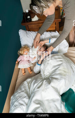 Mother taking temperature of sick daughter lying in bed - Stock Photo