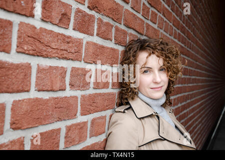 Portrait of woman with curly hair wearing beige trenchcoat leaning against brick wall - Stock Photo