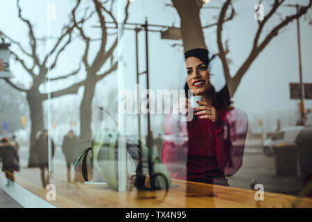 Smiling young woman with cup of coffee behind windowpane in a cafe - Stock Photo