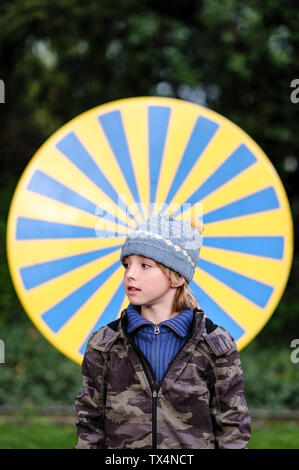 Portrait of boy wearing warm clothing standing in front of yellow and blue circle - Stock Photo