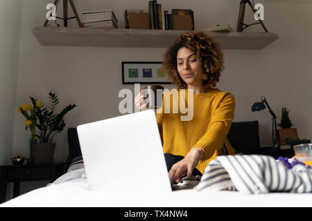 Woman sitting on bed, using laptop, drinking coffee - Stock Photo