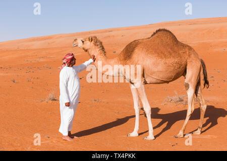 Bedouinn stroking his camel in the desert, Wahiba Sands, Oman - Stock Photo