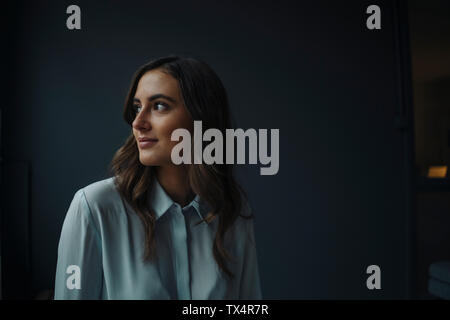 Portrait of smiling young businesswoman looking sideways - Stock Photo