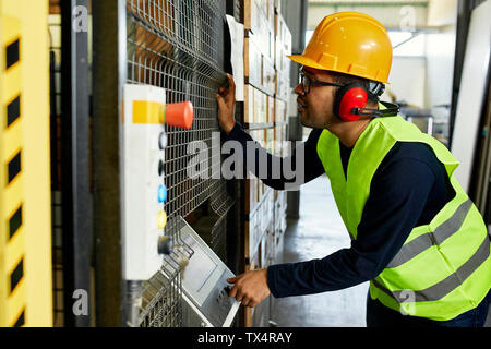 Man operating machine in industrial factory - Stock Photo