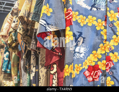 Milan - Italy. Hawaiian shirts with flowers and surf scenes, ideal for wearing on the beach.For sale at the flea market - Stock Photo
