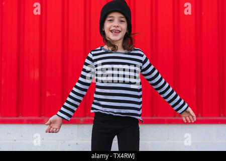 Portrait of happy little girl wearing striped shirt and black cap - Stock Photo