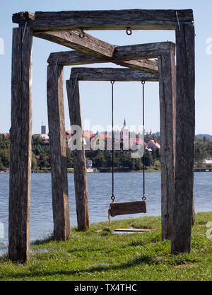 Wooden swing with lake bajer and Fužine town in background - Stock Photo