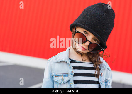 Portrait of little girl wearing black cap and oversized sunglasses - Stock Photo