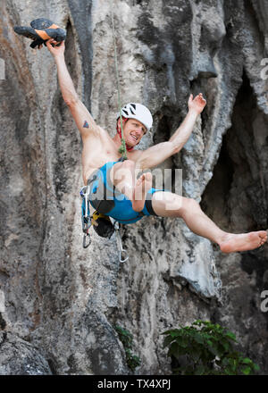 Thailand, Krabi, Lao Liang, barechested climber abseiling from rock wall - Stock Photo