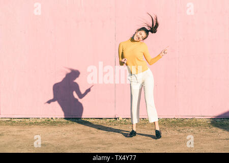Happy young woman dancing in front of a pink wall - Stock Photo