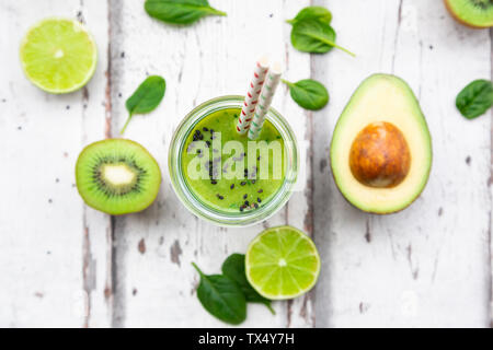 Glass of green smoothie with avocado, spinach, kiwi and lime - Stock Photo