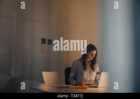 Young businesswoman working late at desk in office
