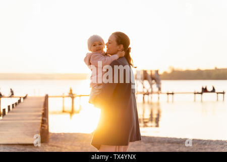 Germany, Bavaria, Herrsching, mother carrying daughter at the lakeshore at sunset - Stock Photo