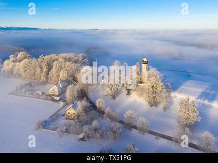 Germany, Bavaria, Holzhausen near Lake Starnberg, foggy winter landscape with church of St. Johann Baptist - Stock Photo