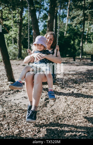 Happy mother with little daughter on swing on a playground