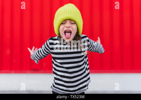 Portrait of little girl wearing striped shirt and yellow cap sticking out tongue in front of red background