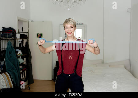 Portrait of smiling woman practicing with fitness band at home - Stock Photo