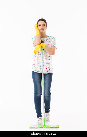 Full length photo of upset housewife 20s wearing yellow rubber gloves for hands protection washing the floor with mop isolated over white background - Stock Photo
