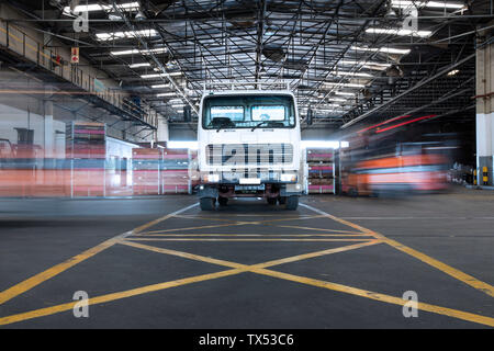 Parked truck in warehouse and moving forklifts - Stock Photo