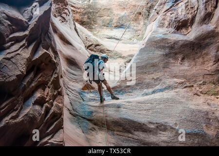 USA, Utah, Moab, Canyonering, Man rapelling down in slot canyon - Stock Photo